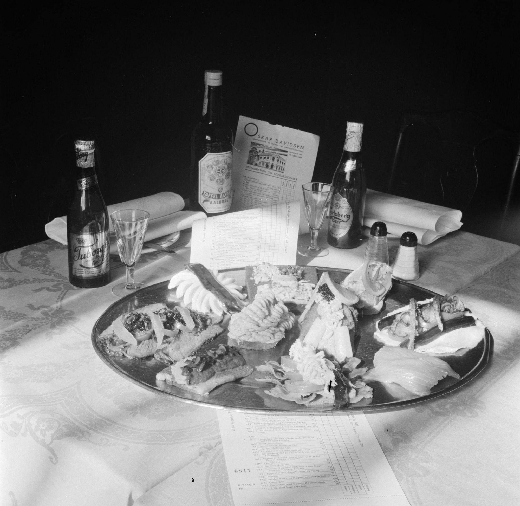 A 1954 photo of various types of smørrebrød, Danish beers, and Aa bottle of Aalborg Taffel Akvavit on it. Photo: Nationaal Archief